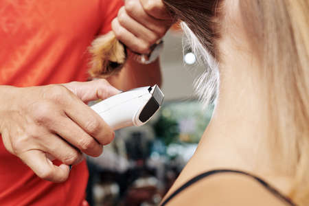 Close-up image of hairdresser shaving hair on nape of female client with electric razor