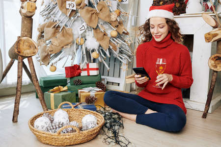 Positive young Caucasian woman sitting on the floor under Christmas tree, drinking champagne and texting with friends
