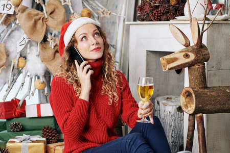Pensive young woman in Santa hat drinking glass of champagne and talking on phone on New Years night Zdjęcie Seryjne - 133359509
