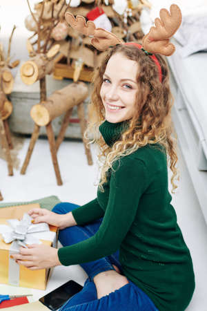 Charming woman in green wool sweater wrapping presents for Christmas celebration