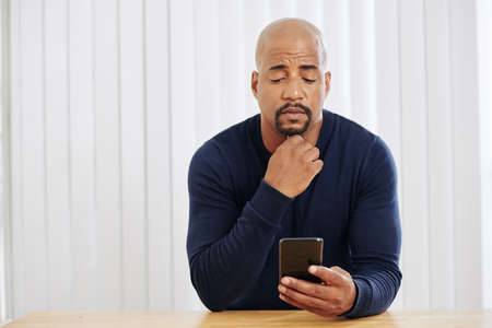 Pensive man scrolling through social media on his smartphone and reading news Banco de Imagens