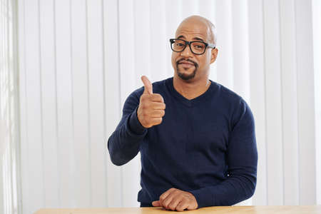 Positive businessman smiling and showing thumbs-up when sitting at office desk