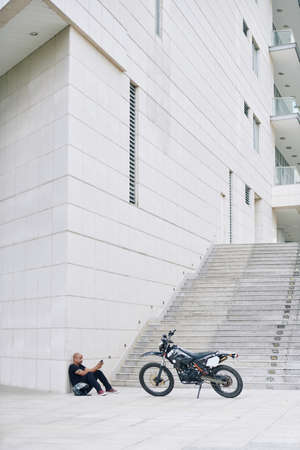 Man sitting on ground near his apartment building after riding on motorcycle and texting friends