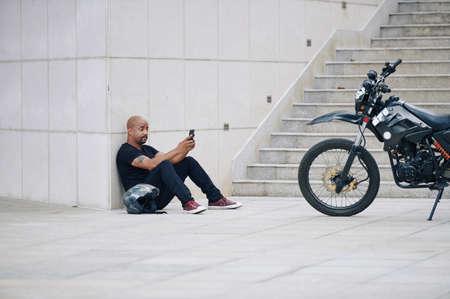 Muskularny mężczyzna w czarnych ubraniach siedzi na ziemi i wysyła SMS-y do znajomych po jeździe motocyklem
