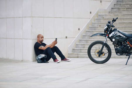 Uomo muscoloso in abiti neri seduto a terra e mandando SMS agli amici dopo aver guidato la moto