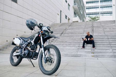 Handsome muscular motorcyclist sitting on steps, drinking take away coffee and checking social media
