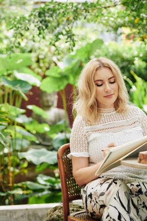 Positive pretty young Caucasian woman drawing in sketchbook when resting among lush greenery