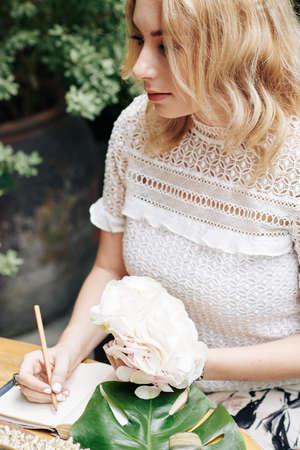 Pensive romantic young woman with blooming flower in hand writing in diary
