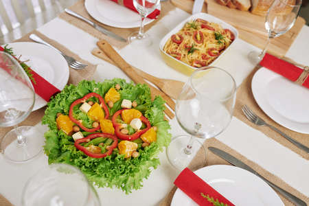 Food, plates, glasses and silverware on table served for Christmas dinner Stock Photo