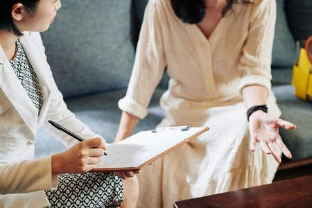 Schoonheidsspecialist die vrouwelijke klanten vragen stelt over haar levensstijl en gewoonten en vragenlijst invult