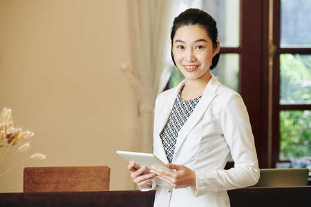 Young lovely spa salon receptionist standing at workplace with tablet computer in hands