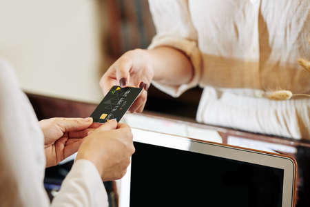 Credit card in hands female receptionist returning it to client after accepting payment