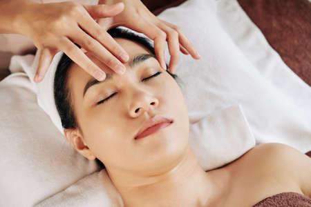 Beautiful young Vietnamese woman receiving anti-aging face massage in beauty salon