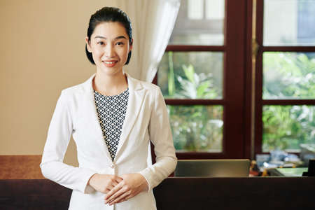 Positive young pretty spa salon receptionist standing at workplace and smiling at camera