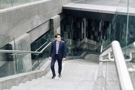 Handsome young Asian businessman walking up the metro station or underground crossing