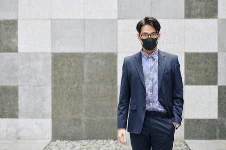 Serious businessman in black protective face mask waiting for train at station