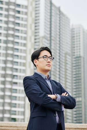 Entrepreneur pensif confiant sérieux croisant les bras lorsqu'il se tient à l'extérieur dans le nouveau quartier