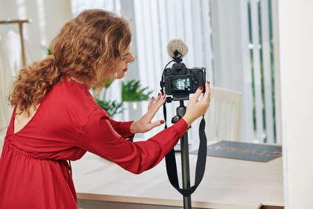 Blogger de belleza joven en vestido rojo instalando una cámara digital frente a su escritorio para hacer un video para su blog