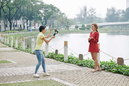 Two female friends shooting video on smartphone on bank of city river