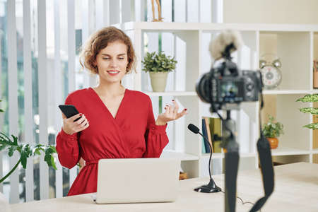 Beautiful young woman with smartphone in hand looking at laptop screen and recording webinar for her subscribers