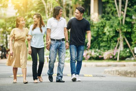 Glückliche vietnamesische Eltern mittleren Alters und erwachsene Kinder, die auf der Straße spazieren und über Neuigkeiten diskutieren