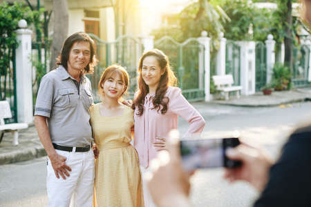 Happy Asian middle-aged parents posing with their adult daughter for photo on smartphone
