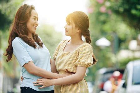 Happy mature Vietnamese woman looking at her smiling beautiful adult daughter