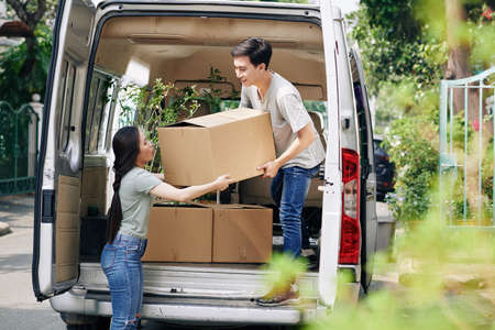 Young Asian woman helping boyfriend to take cardboard box out of car