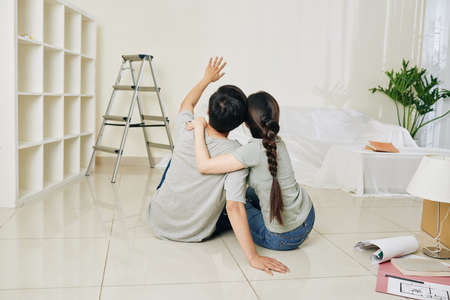 Cheerful young hugging couple sitting on the floor in new apartment and discussing ideas for renovation