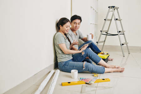 Young Asian couple sitting at wall, drinking coffee and discussing plan of apartment renovation on tablet computer Banco de Imagens