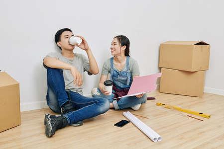 Fröhliches junges vietnamesisches Paar, das in einer neuen Wohnung auf dem Boden sitzt, Kaffee zum Mitnehmen trinkt und den Umbauplan bespricht Standard-Bild