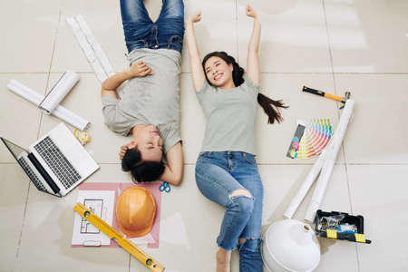 Happy satisfied young Vietnamese couple resting on the floor after planning home renovation, view from above
