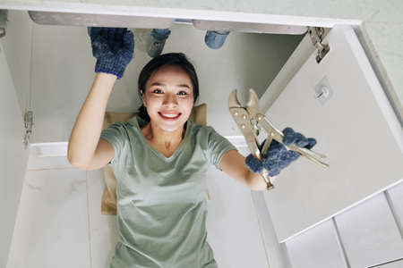 Smiling young pretty Vietnamese woman using wrench when fixing pipe problem in her kitchen