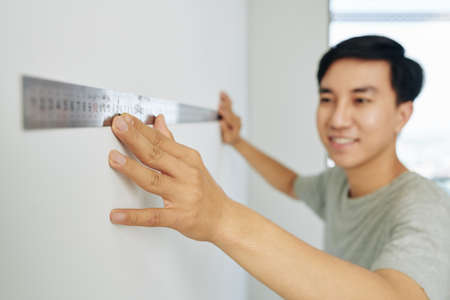 Smiling young man using metal ruller when measuring walls in his apartment