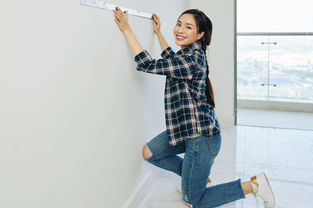 Beautiful young Vietnamese woman in jeans and plaid shirt measuring walls with metal ruller 스톡 콘텐츠