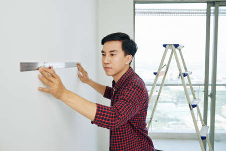 Serious young Asian man measuring walls in his new house with metal ruller before start painting