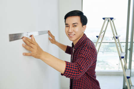 Handsome cheerful Vietnamese man in plaid shirt using metal ruller when preparing for house renovation