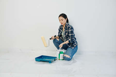 Beautiful young Asian woman pouring white paint in plastic tray and applying it with roller