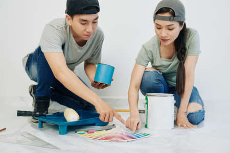 Young Asian couple in jeans and t-shirts choosing color for painting walls in their new apartment