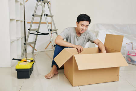 Handsome young Asian man unpacking tools in new apartment he is going to remodel
