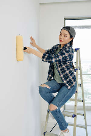 Pretty young Vietnamese woman in cap and plaid shirt sitting on ladder and painting wall with roller