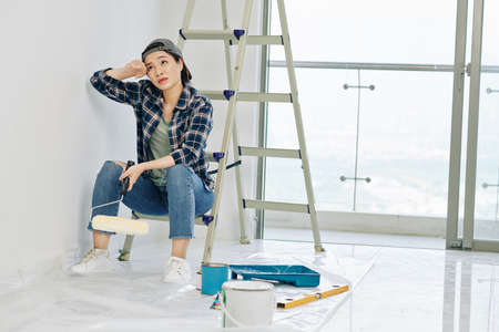 Exhausted young Vietnamese woman almost crying when having short break after painting walls in apartment