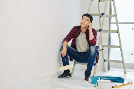 Pensive tired young Vietnamese man with roller in hand sitting on ladder and looking at wall he just painted