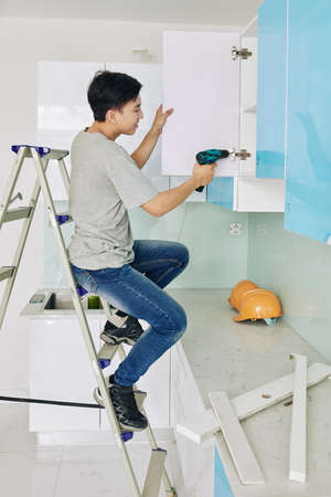 Young Asian man sitting on ladder when fixing door of kitchen cupboard