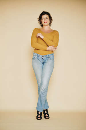 Photo shoot of positive pretty woman in jeans and high heels posing in studio