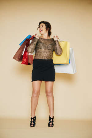 Happy woman in short dress and high heels standing with many shopping bags