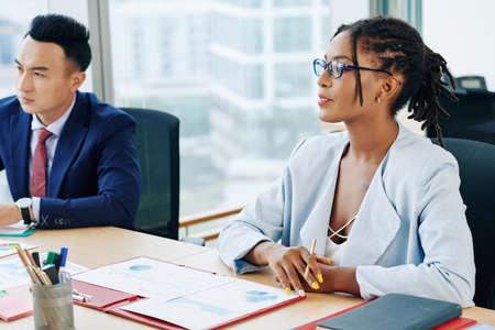 Mooie zakenvrouw met dreadlocks zittend aan grote tafel met collega's en financiële documenten bespreken tijdens vergadering Stockfoto