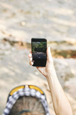 Hand of tourist using camera on smartphone when taking photos of nature during weekend hike
