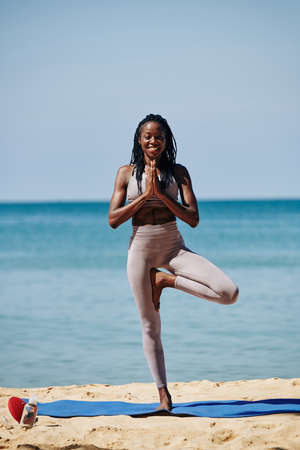 Feliz joven mujer negra delgada de pie en el árbol asana y tomados de la mano en gesto de namaste Foto de archivo