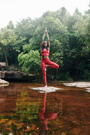Slim fit young woman standing on one leg on rock in the creek and doing tree asana 版權商用圖片
